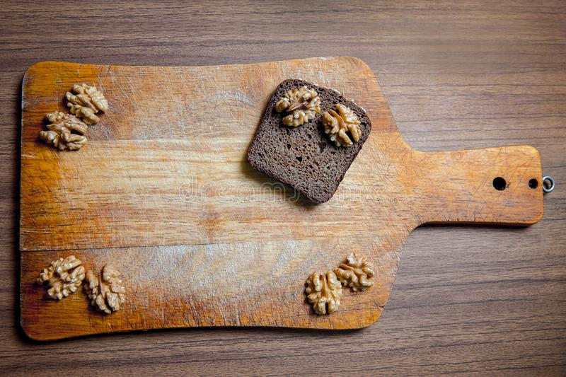 A piece of black rye bread with walnuts on a wooden chopping Board stock photo