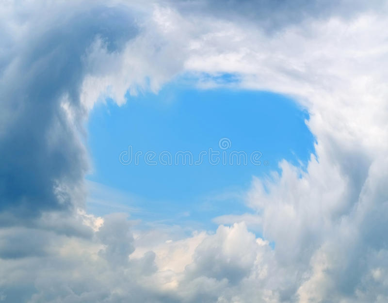Piece of blue sky framed by clouds stock photography