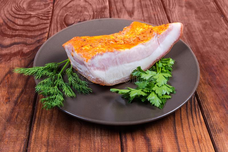 Piece of boiled smoked pork belly on dish with greens stock photography