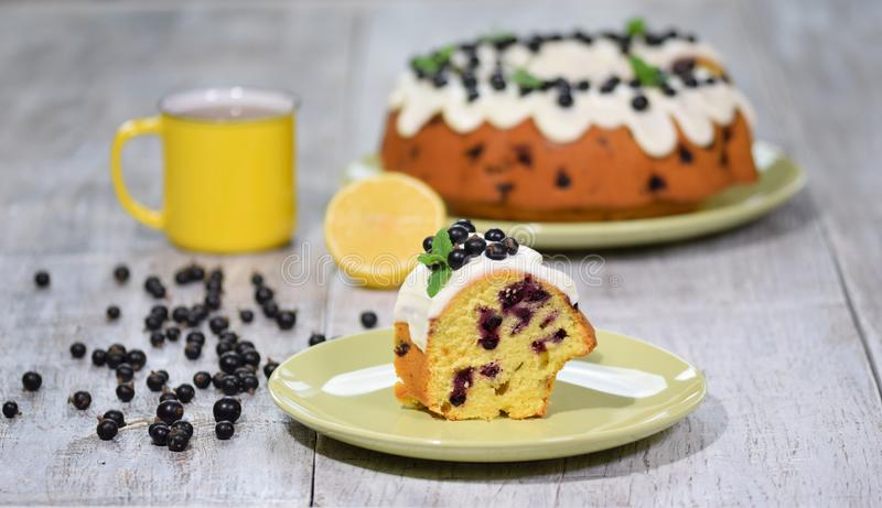 Piece of bundt cake with black currant and glaze royalty free stock image