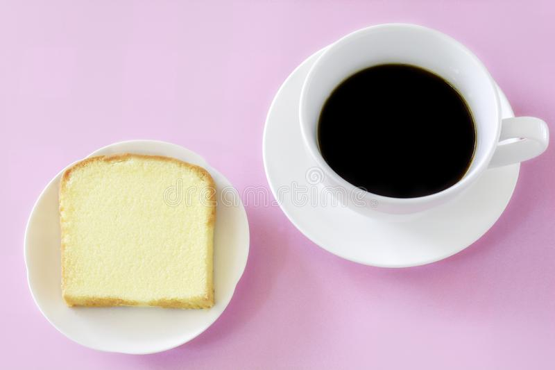 Piece of butter cake on white dish served with cup of black coffee. Times to relax concept royalty free stock image