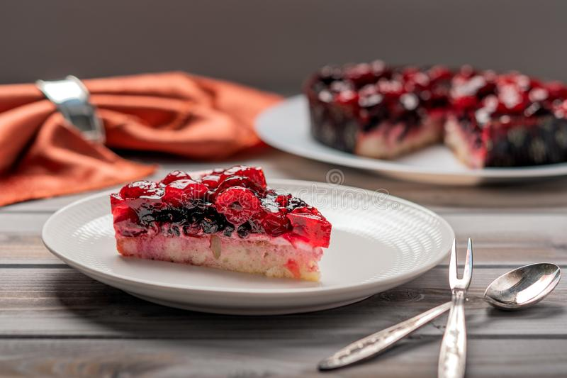 Piece of cake with berries: raspberry, currant, strawberry on a white plate, next to dessert spoon and fork, on a wooden stock photography