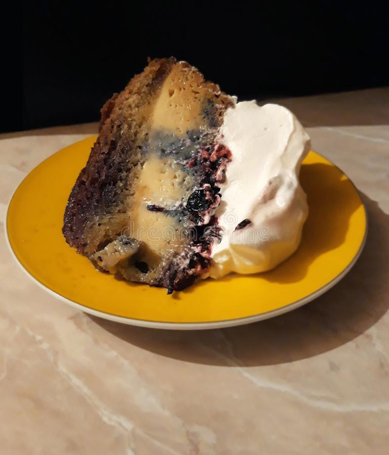 Piece of cake with blueberries and whipped cream on a yellow plate royalty free stock photos