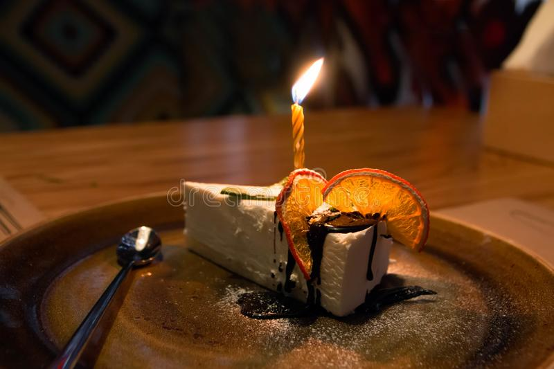 A piece of cake with candles, for birthday with oranges stock photos