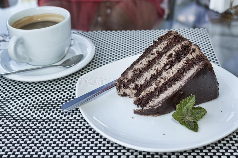 A piece of cake in chocolate glaze sideways and mint leaves stock photo