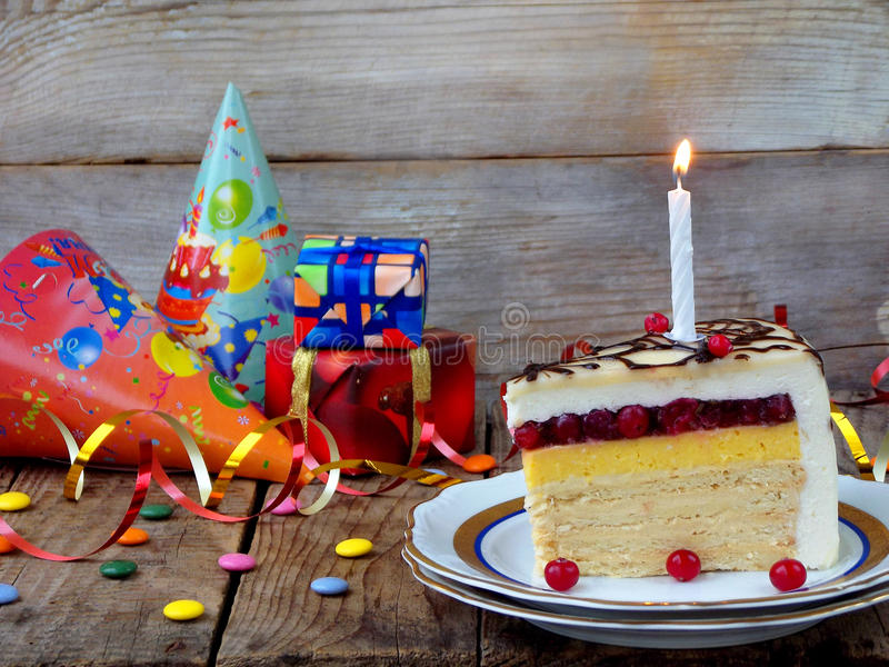 Piece of cake `Napoleon` with lighted candles. Birthday. Side view. Copy space. Selective focus royalty free stock images