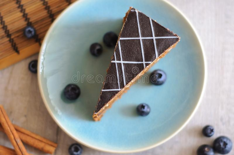 A piece of cake on a plate, blueberries and cinnamon sticks. royalty free stock photo