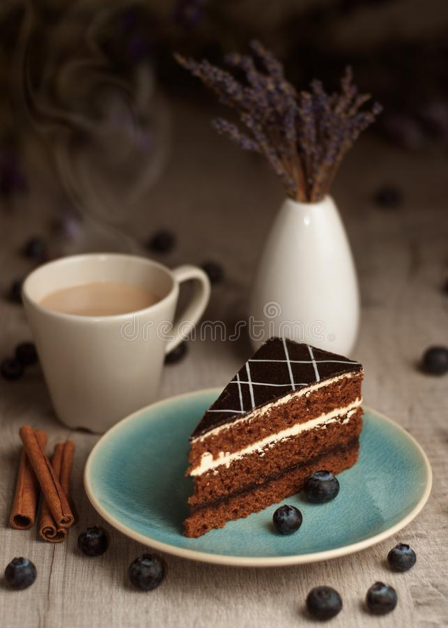 A piece of cake on a plate and a cup of coffee. royalty free stock photography