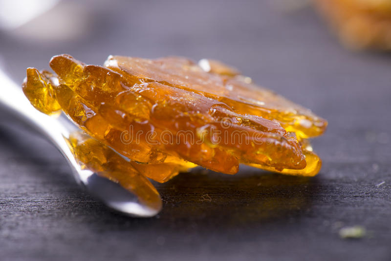 Piece of cannabis oil concentrate aka shatter with dabbing tool royalty free stock images