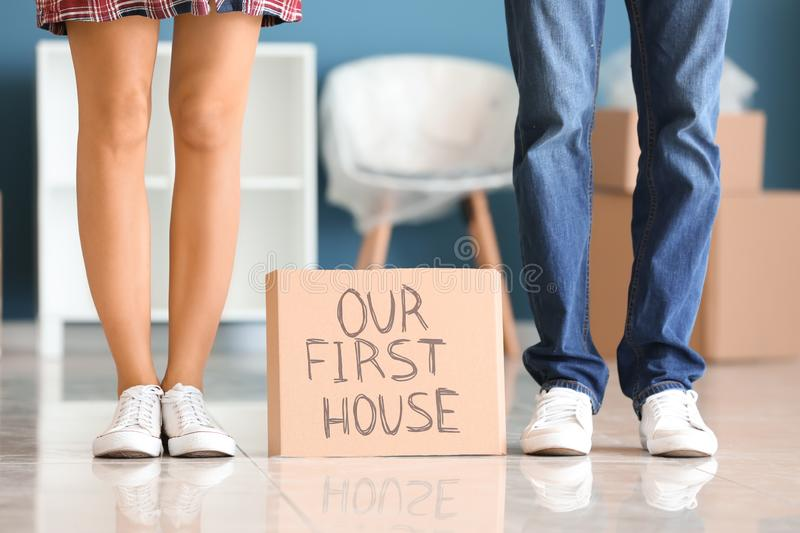 Piece of cardboard with text OUR FIRST HOUSE and young couple indoors royalty free stock photo