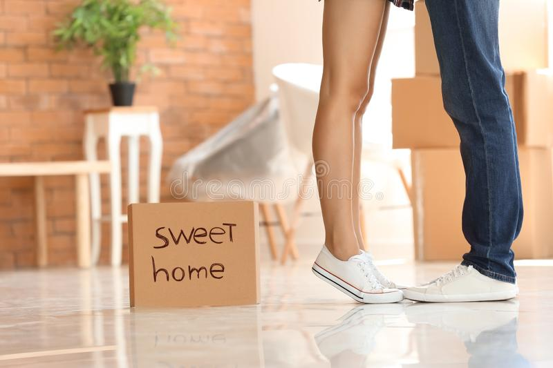Piece of cardboard with text SWEET HOME and young couple indoors royalty free stock photos