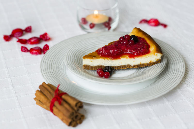 Piece of cheesecake with red and black berries on top of it on white plate with cinnamon sticks with red string and burning candle stock image