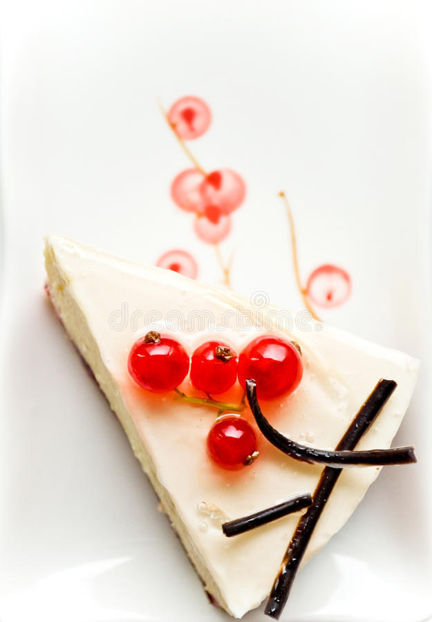 Piece of cheesecake with red currant stock photos