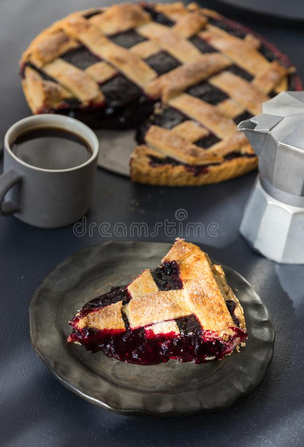 A piece of cherry pie lies on a ceramic plate and a cup of coffee with milk jug stand on the table stock photos