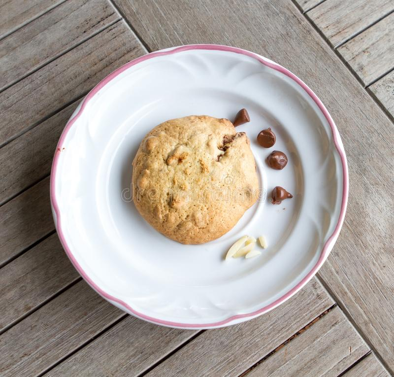 A piece of choc chip cookie. Chocolate chip cookie on a white plate stock photos