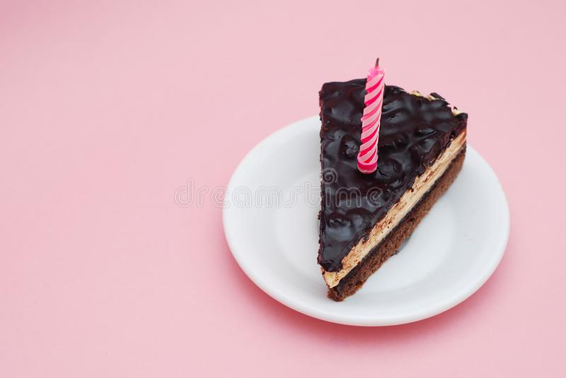 Piece of Chocolate Birthday Cake with Candle on White Plate over Pink Background for Text. Horizontal. Party and stock images