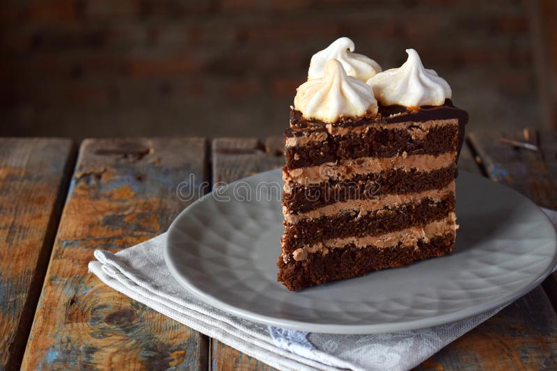 Piece of Chocolate cake decorated with rosettes of meringue cream: chocolate-nut biscuit, caramel cream. Homemade baking royalty free stock photography