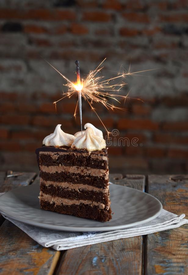 Piece of Chocolate cake decorated with rosettes of meringue cream: chocolate-nut biscuit, caramel cream. Homemade baking royalty free stock photos