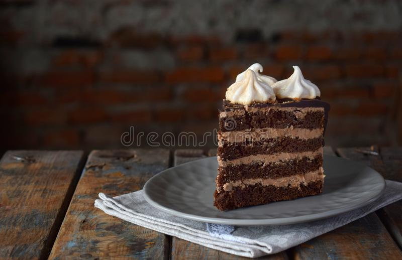 Piece of chocolate cake decorated with rosettes of meringue cream: chocolate-nut biscuit, caramel cream. Homemade baking royalty free stock image