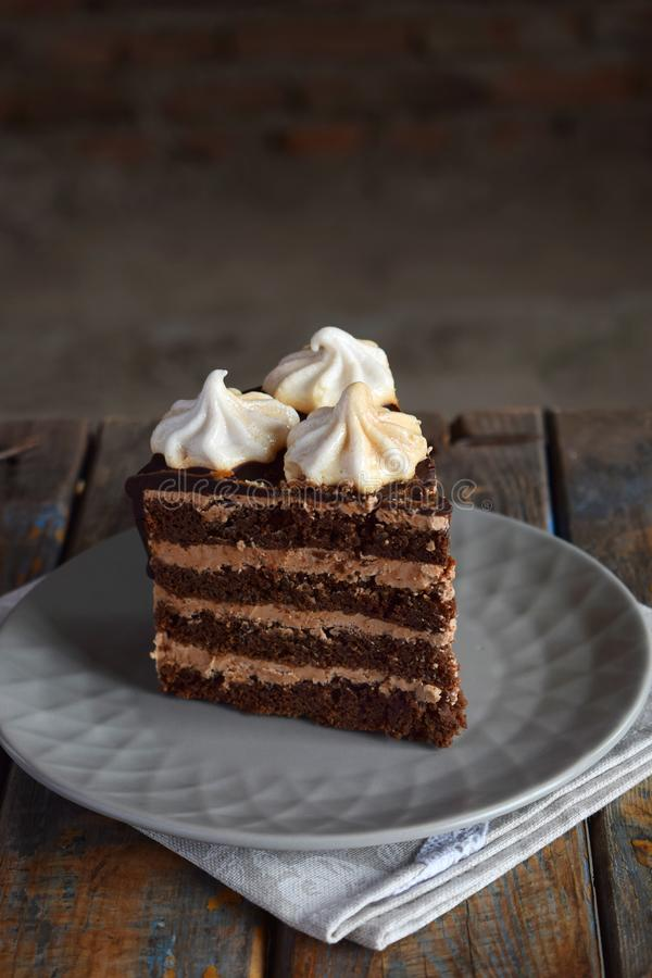 Piece of chocolate cake decorated with rosettes of meringue cream: chocolate-nut biscuit, caramel cream. Homemade baking stock images