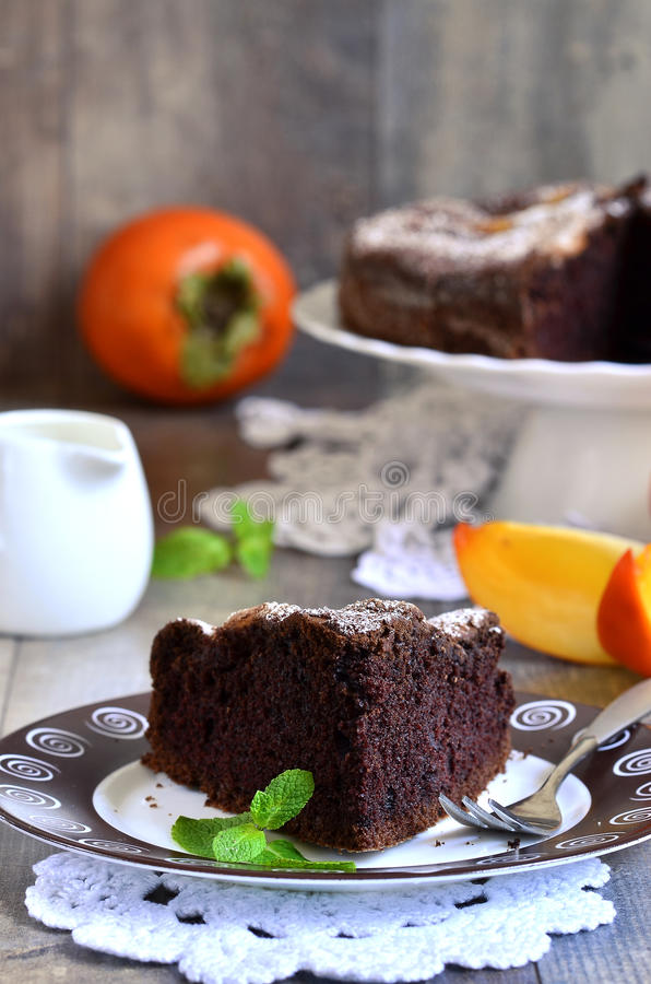 Piece of a chocolate cake with persimmon. stock photo