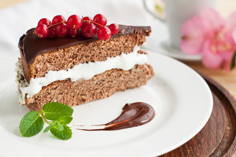 Chocolate Cake with red currant. Piece of Chocolate Cake with whipped cream and chocolate icing decorated with branch of red currant stock photo