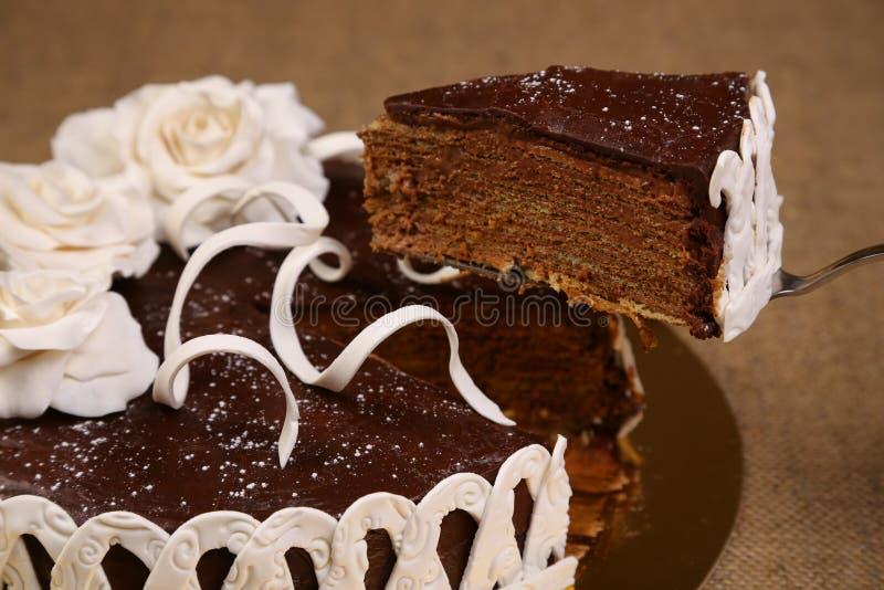 Piece of chocolate cake. White fondant flowers decoration. Bakery. Sweet food. Homemade cake royalty free stock photo