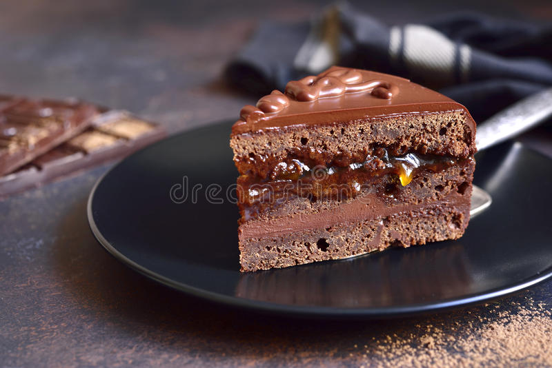 Piece of chocolate Sacher torte on a black plate on a slate,stone or metal background. stock images
