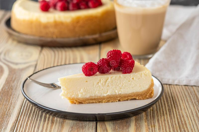 Piece of classic cheesecake with raspberries and coffee on a wooden background. Copy space. royalty free stock photo