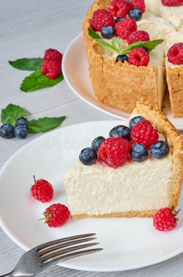 A piece of classic New York cheesecake with fresh raspberries, blueberries and mint leaves on the white plate on the gray table royalty free stock photography