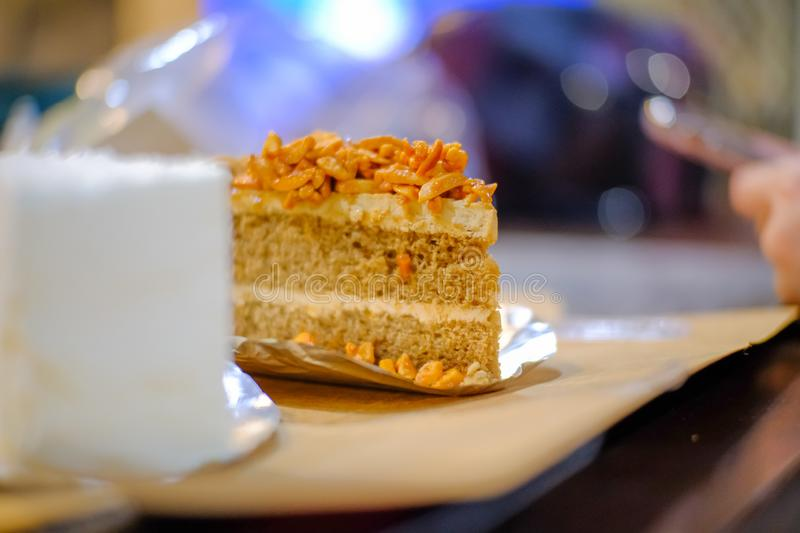 Piece of coffee almond cake on a plate. At cafe stock images