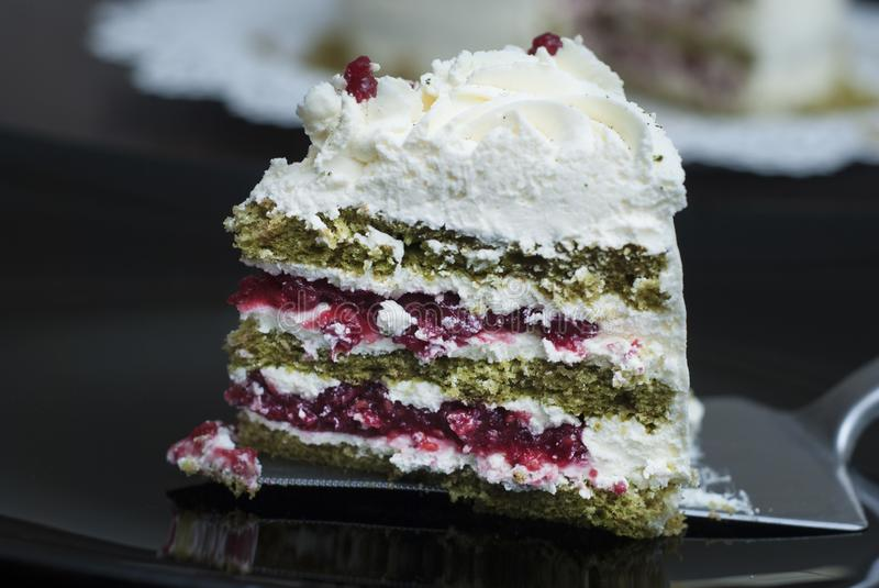 Piece of Colorful Strawbery Cake with white cream and Green Tea, on Black Plate. Unique Homemade Cake Recipe. stock photography