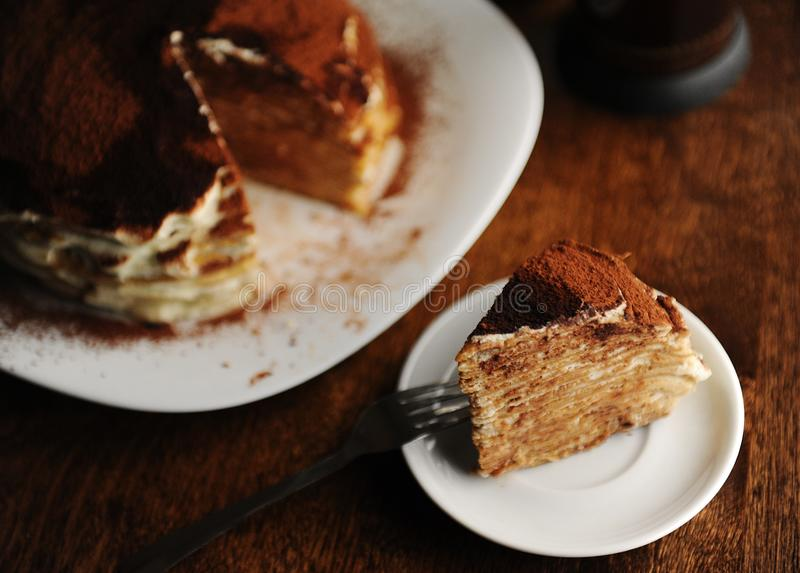 Piece of crepe cake with tiramisu filling and powdery cocoa is served on plate. The interior of coffee shop. Piece of crepe cake with tiramisu filling and stock image