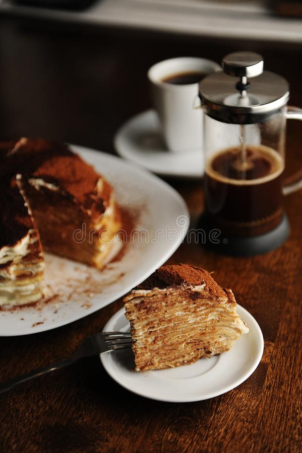 Piece of crepe cake with tiramisu filling and powdery cocoa is served on plate. The interior of coffee shop. Piece of crepe cake with tiramisu filling and royalty free stock photos