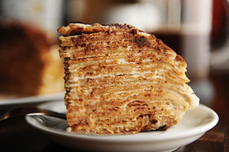 Piece of crepe cake with tiramisu filling and powdery cocoa is served on plate. The interior of coffee shop. Piece of crepe cake with tiramisu filling and stock photography
