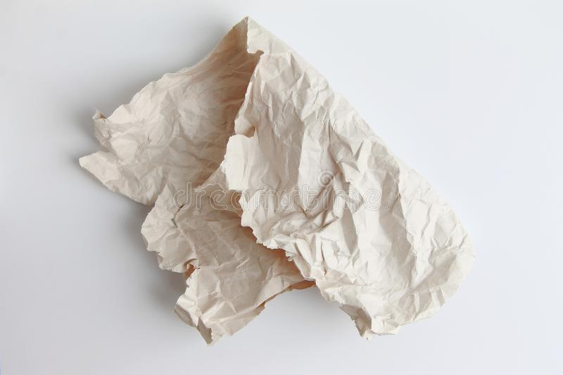 A piece of crumpled paper is folded in half on a light background. stock photography