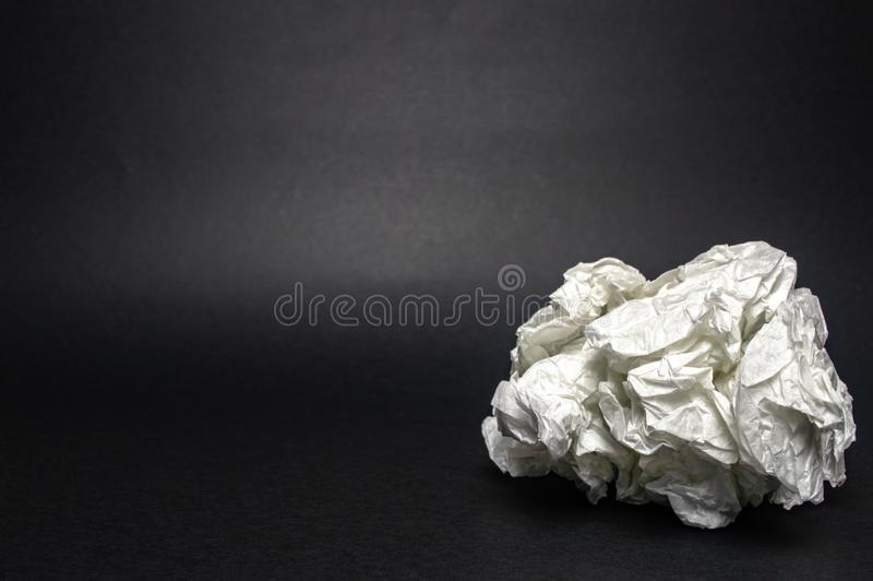 A piece of crumpled white paper on black closeup texture royalty free stock images