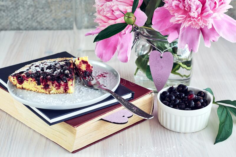 A piece of currant pie. A piece of homemade currant pie in a plate on books and a bouquet of pink peonies, summer day royalty free stock image