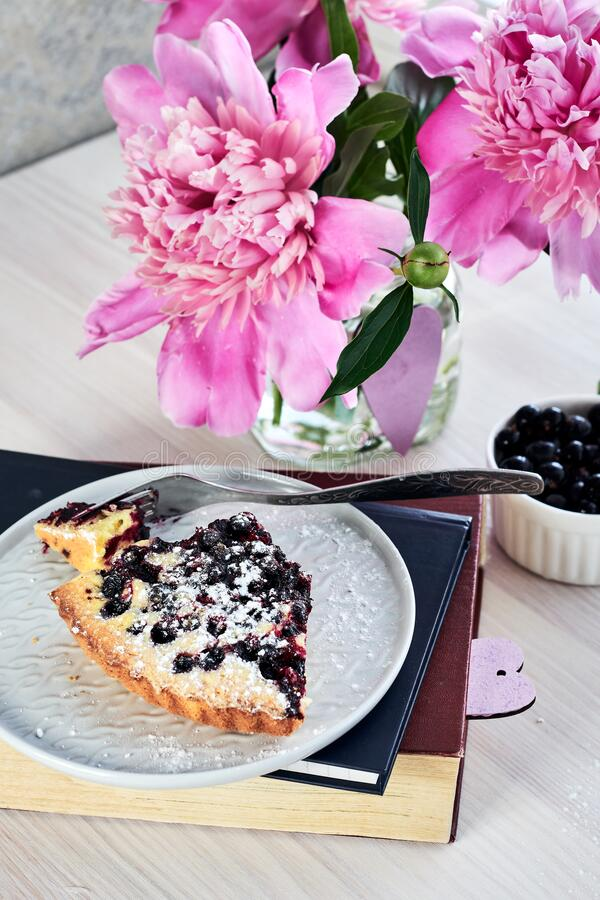 A piece of currant pie. A piece of homemade currant pie in a plate on books and a bouquet of pink peonies, summer day stock photos