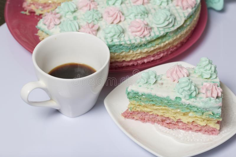 The piece is cut off and lies side by side on a saucer. Nearby is a cup of coffee. Waffle cake made from cream soaked cakes. royalty free stock photo
