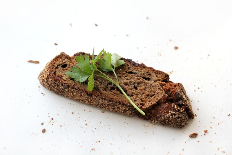 A piece of dark bread with cranberries and a sprig of parsley on a white background with free space for text. royalty free stock images