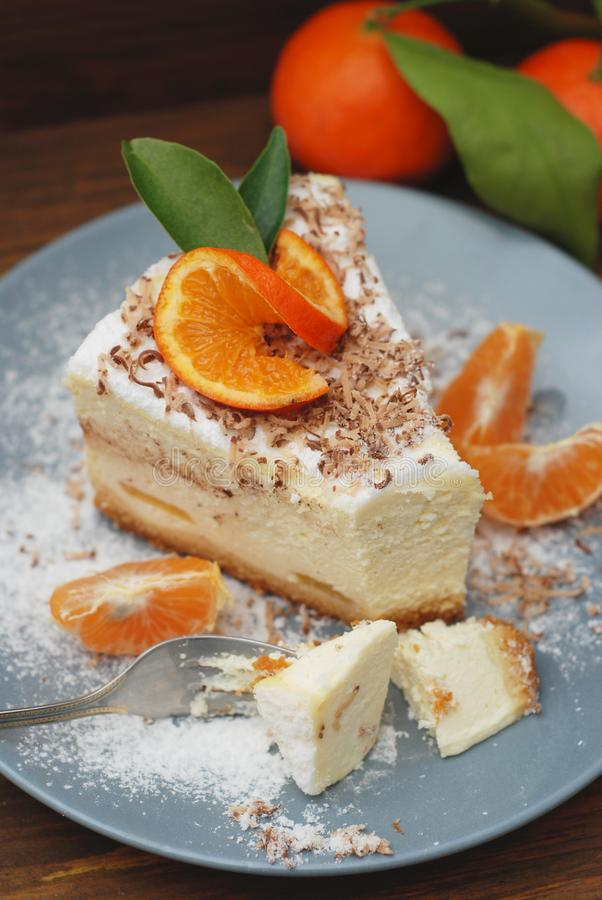 Piece of Delicious Cheesecake with Tangerine on Gray Plate and Dark Wooden Background. Vertical Image. stock photography