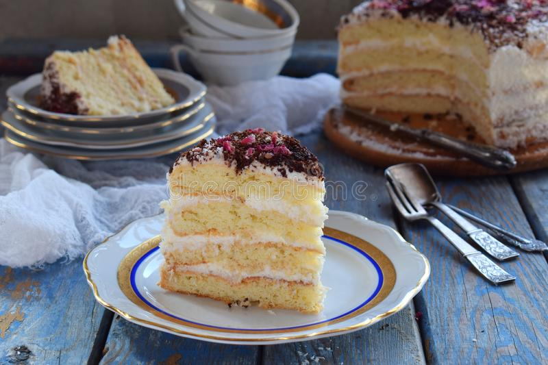 A piece of delicious coconut layer cake - a biscuit and cream on coconut cream, decorated with grated chocolate and candied rose. Piece of delicious coconut stock photography