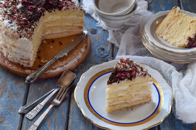 A piece of delicious coconut layer cake - a biscuit and cream on coconut cream, decorated with grated chocolate and candied rose. Piece of delicious coconut royalty free stock image