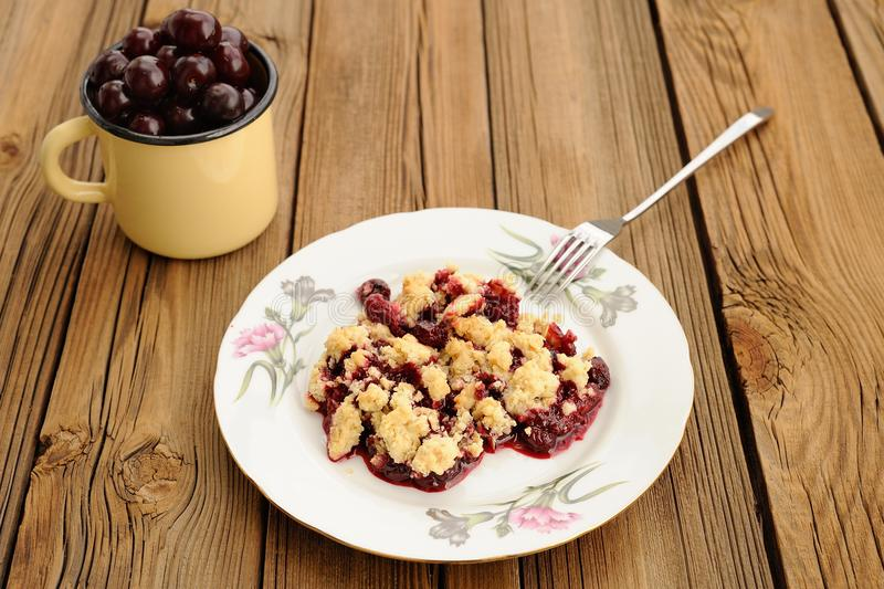 Piece of delicious homemade cherry crumble with fork in white pl royalty free stock photography