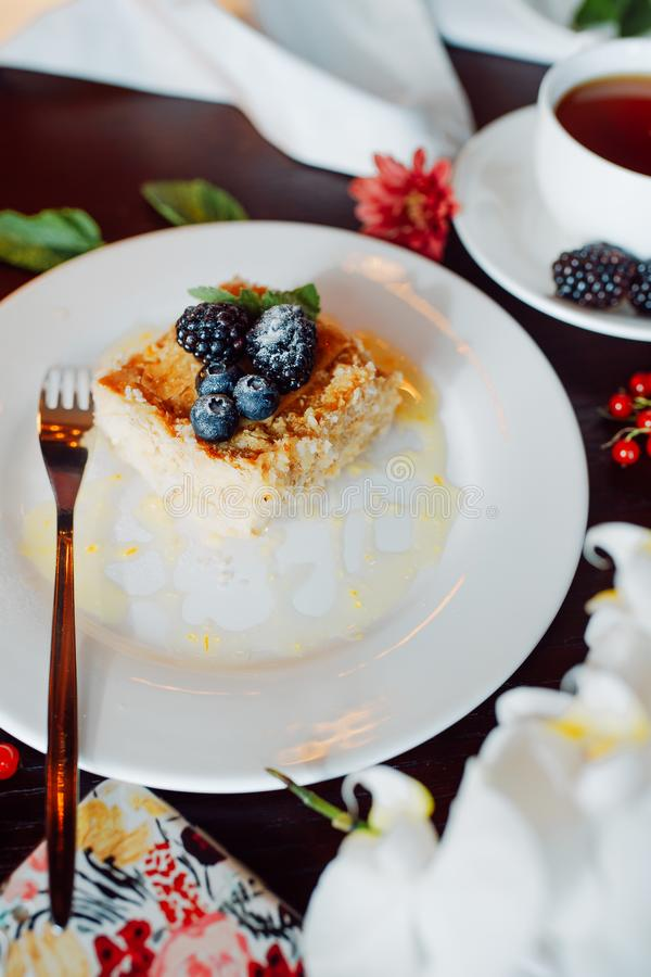 A piece of delicious Napoleon, decorated with blackberries and blueberries stock photo