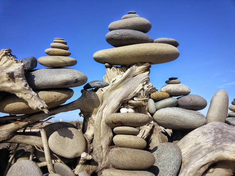 Mysterious Stacked Stones on the Dungeness Spit. An piece of driftwood acts a pedestal for stacking stones found on the beach along the Dungeness Spit located in stock image