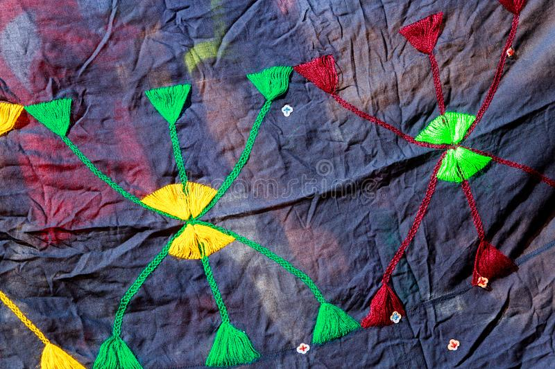 A piece of dyed cloth with the symbol motif of the Moroccan Berber people stitched in bright colors. stock photography