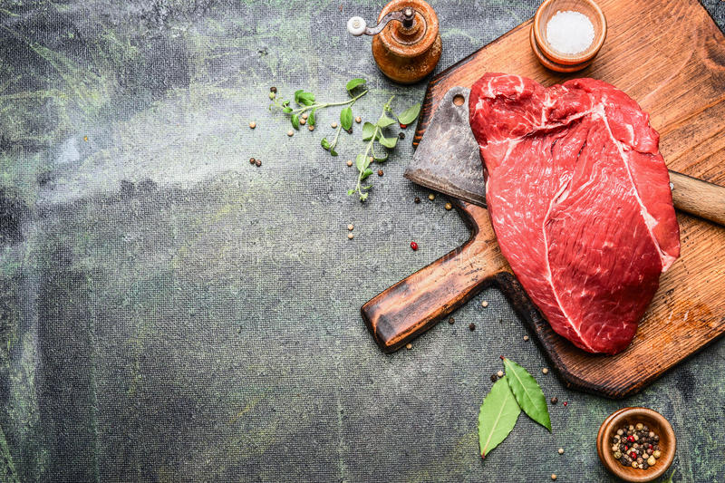 Piece of excellent raw meat on cutting board with herbs and spices for cooking or grill on rustic background, top view. Place for text, border royalty free stock photos