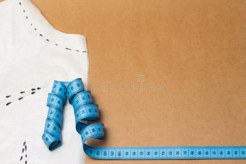 piece of fabric with lace, measuring tape and colored thread on kraft paper background royalty free stock photos